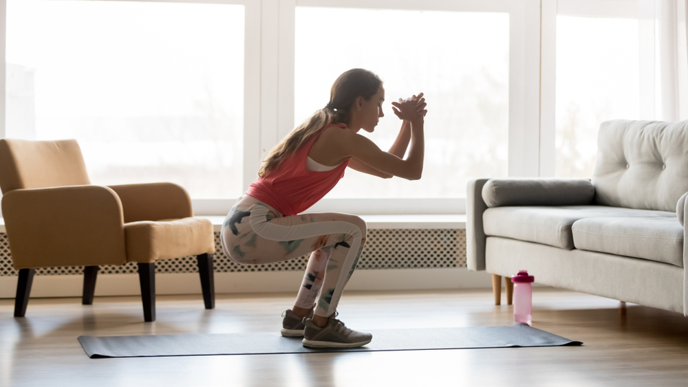 woman doing a squat on mat indoors